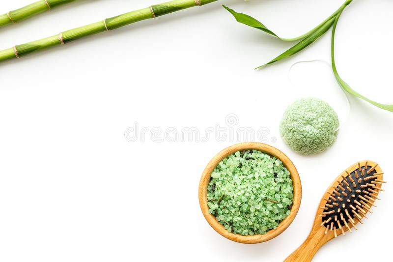 Asian spa treatment concept with natural ingredients. Spa salt, lotion, sponge near bamboo on white background top view stock photography