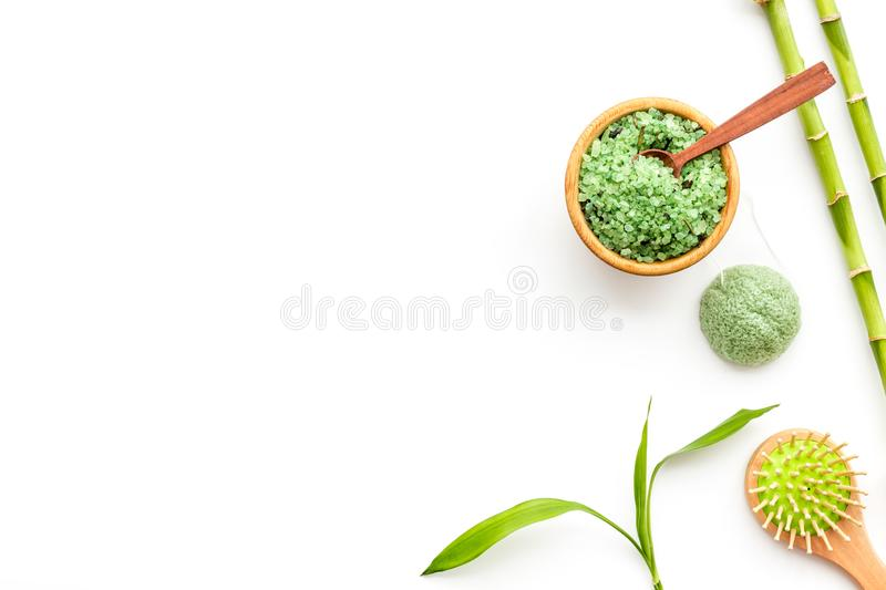 Asian spa treatment concept with natural ingredients. Spa salt, lotion, sponge near bamboo on white background top view.  stock images