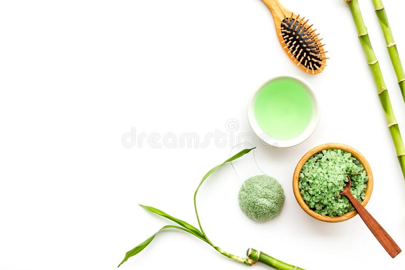 Asian spa treatment concept with natural ingredients. Spa salt, lotion, sponge near bamboo on white background top view royalty free stock photography