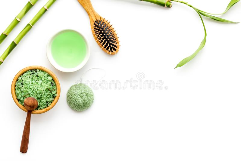 Asian spa treatment concept with natural ingredients. Spa salt, lotion, sponge near bamboo on white background top view.  royalty free stock photo
