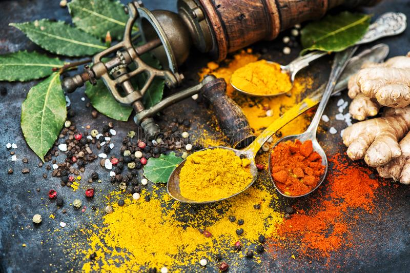 Asian spices dark table background Curry turmeric ginger bay lea. Asian spices on dark table background. Curry, turmeric, ginger, bay leaf. Healthy organic food stock images
