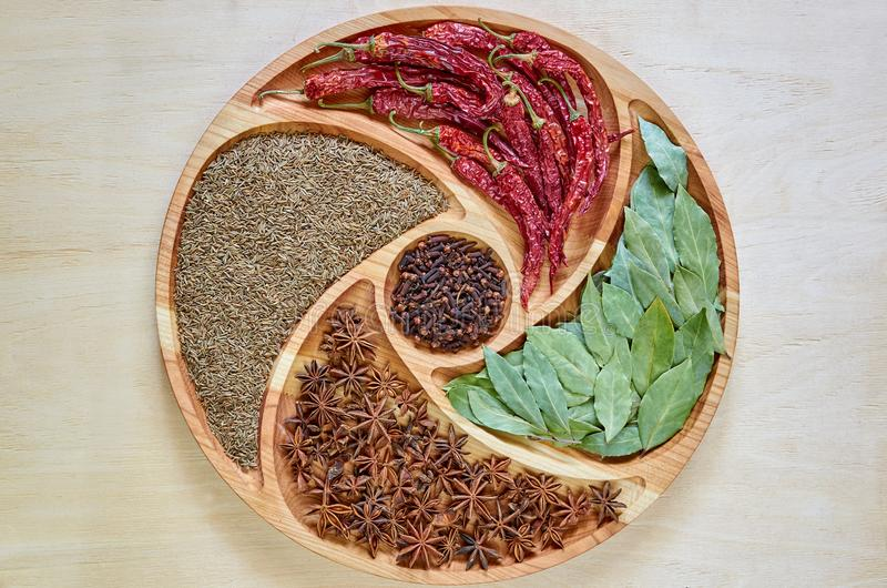 Asian spices on the wooden plate: star anise, bay leaves, paprika, dried cloves and cumin close up. Spices texture background stock images