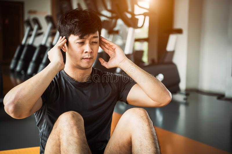 Asian sport man doing crunch or sit up posture on yoga mat in fitness gym at condominium with gym equipment background. Office royalty free stock images