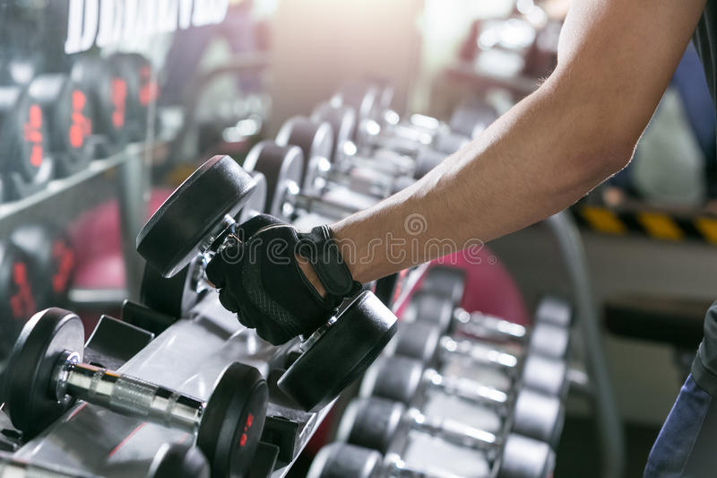 Asian sport man doing one-arm dumbbell rows of metal in modern g royalty free stock image