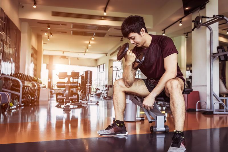 Asian sport man lifting dumbbell at fitness bench with gym equipment background. Sport exercise and People lifestyles concept royalty free stock photos