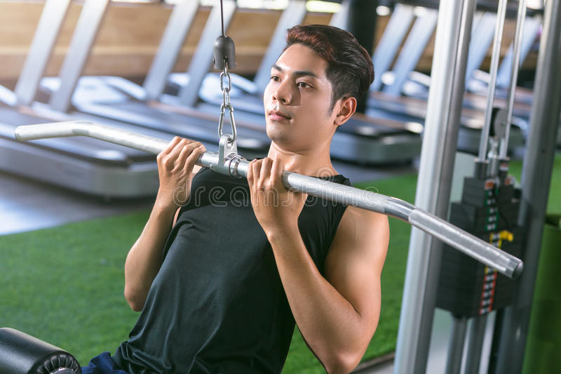 Asian sport man making elevations. Bodybuilder training in gym royalty free stock image