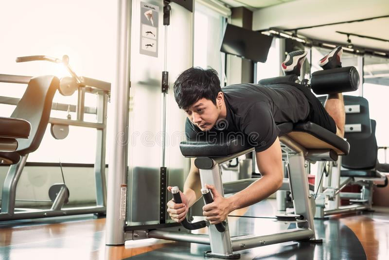 Asian sport man stretching and lifting weight by two legs when facing down for stretching muscle at fitness gym at condominium stock photography