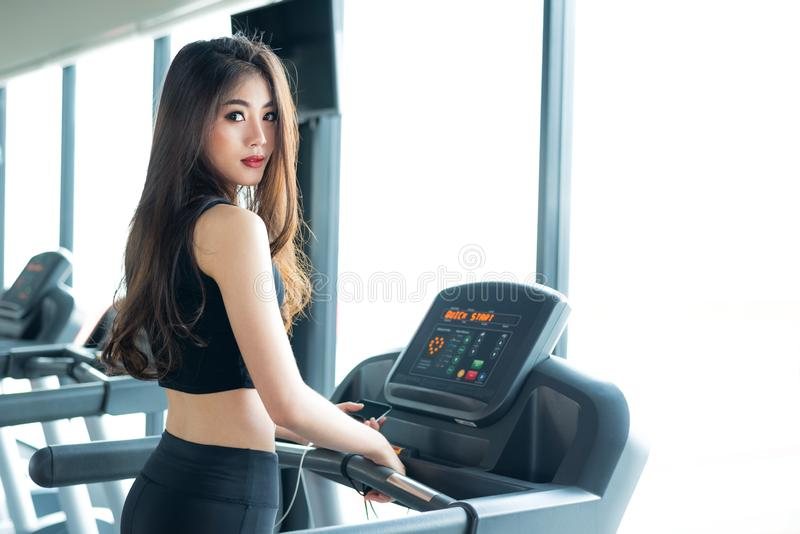 Asian sport woman walking or running on treadmill equipment in fitness workout gym. Sport and Beauty concept. Workout and Strength stock photography