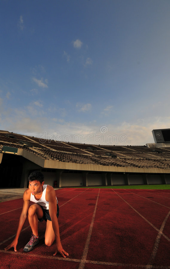 Asian Sports Man preparing to Run race in stadium stock photo