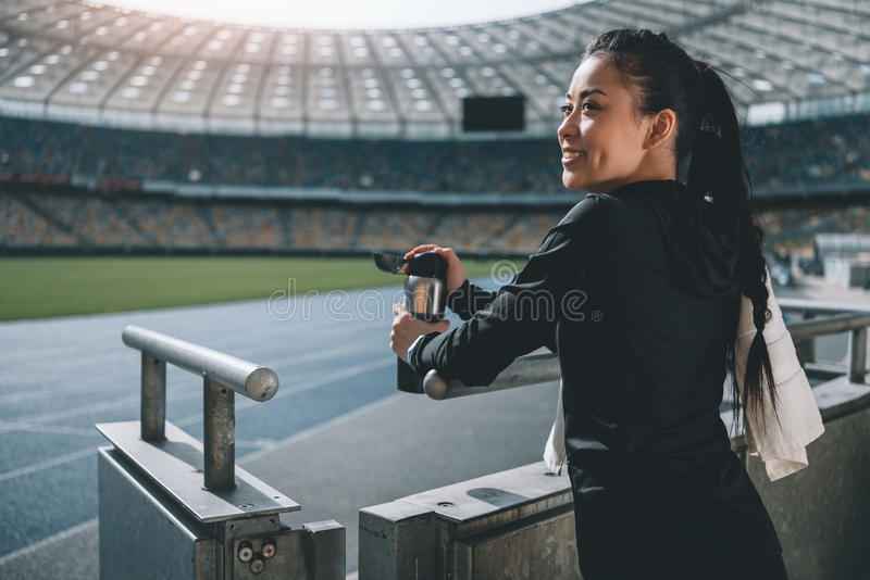 Asian sportswoman with sport bottle and towel on stadium. Happy asian sportswoman with sport bottle and towel on stadium royalty free stock photos