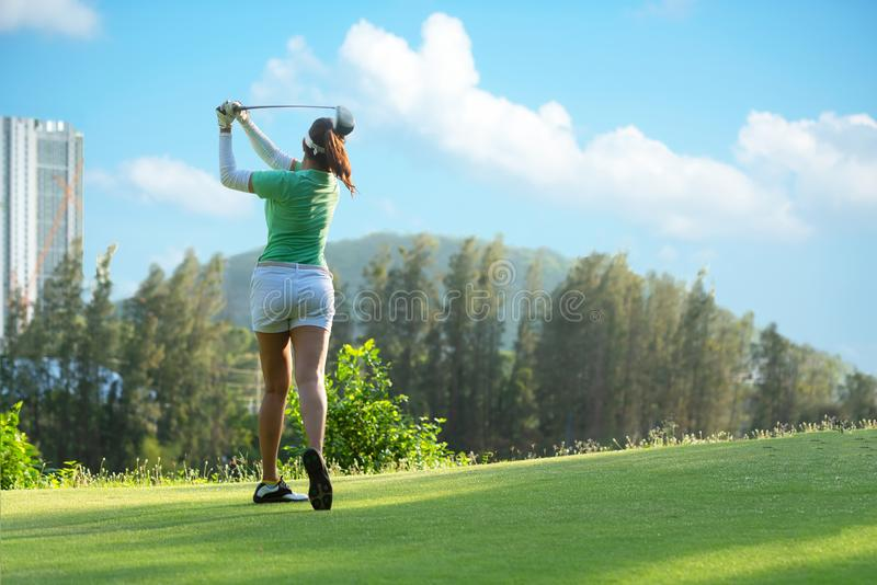 Asian  Sporty woman golfer player doing golf swing tee off on the green, people presumably does exercise. stock photo