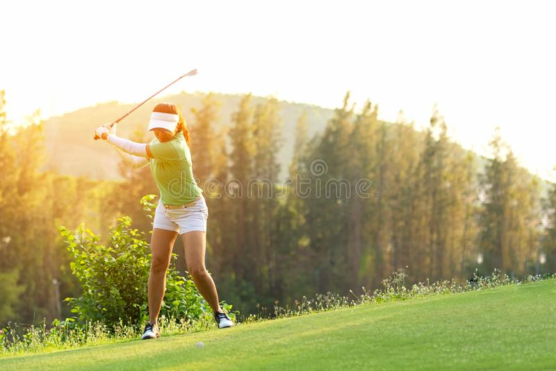 Asian Sporty woman golfer player doing golf swing tee off on the green, people presumably does exercise. Healthy Sport royalty free stock images
