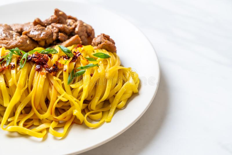 Asian stir-fried noodle with pork. And chili paste royalty free stock photo
