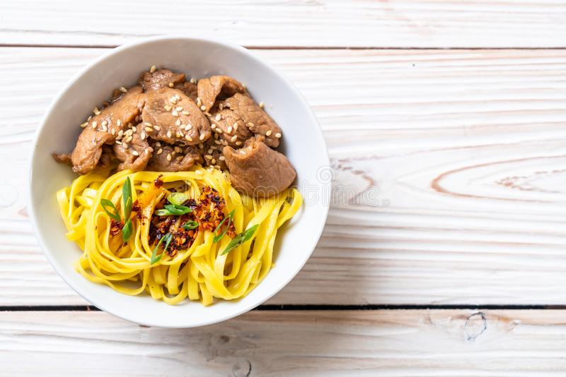 Asian stir-fried noodle with pork. And chili paste royalty free stock image