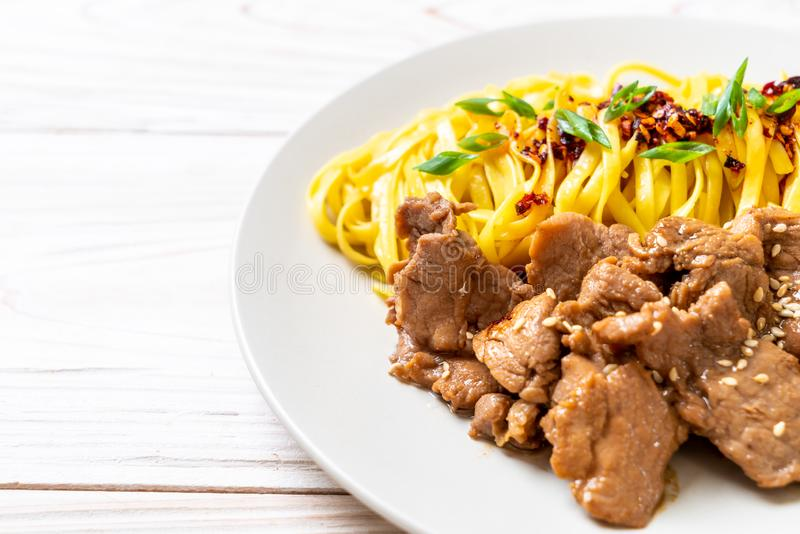 Asian stir-fried noodle with pork. And chili paste stock image