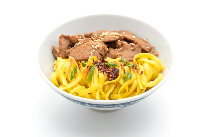 Asian stir-fried noodle with pork. And chili paste isolated on white. background stock image