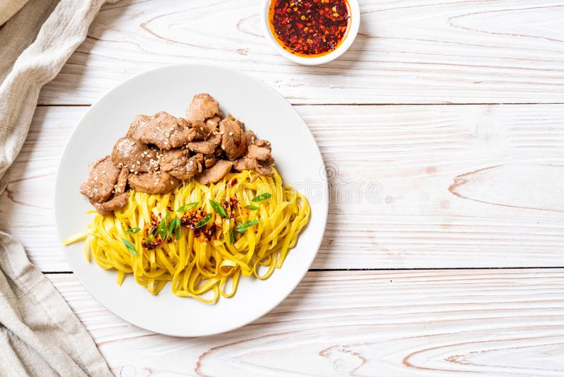 Asian stir-fried noodle with pork. And chili paste stock images