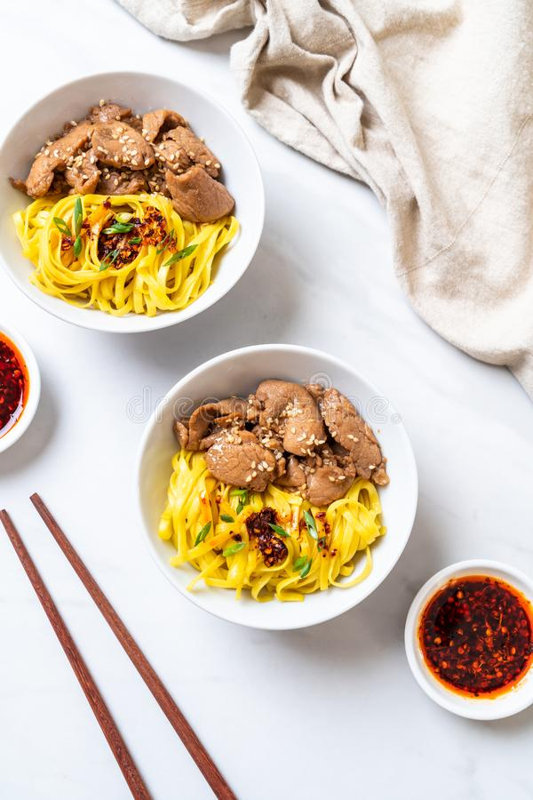 Asian stir-fried noodle with pork. And chili paste stock photo