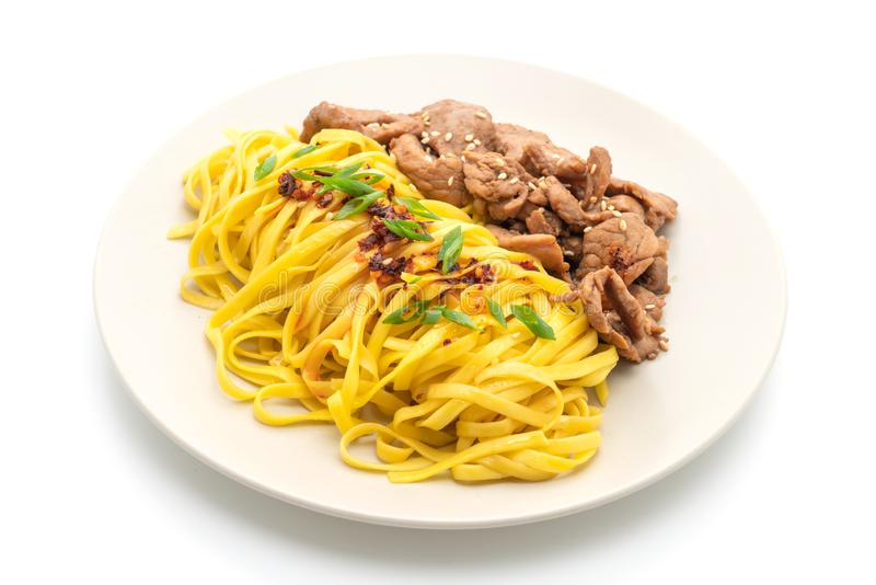 Asian stir-fried noodle with pork. And chili paste isolated on white. background stock photo