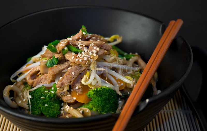 Asian Stir Fry. With Shanghai noodles, pork, vegetables, bean sprouts and seasame seeds, with chopsticks on bamboo mat stock image