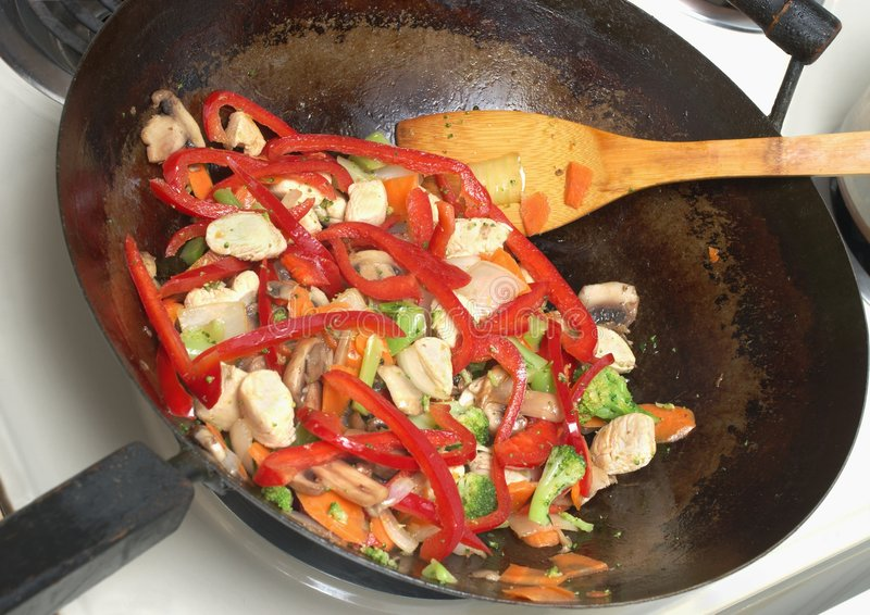 Asian Stir Fry in Chinese Wok. Colorful vegetable stir-fry featuring red peppers and white chicken meat royalty free stock photos
