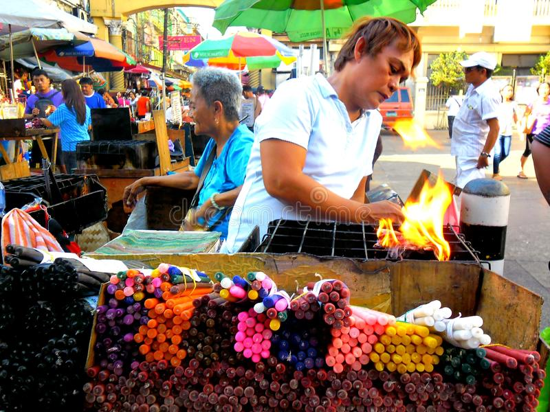 Asian street vendor selling colored candles outside of quiapo church in quiapo, manila, philippines in asia royalty free stock photography