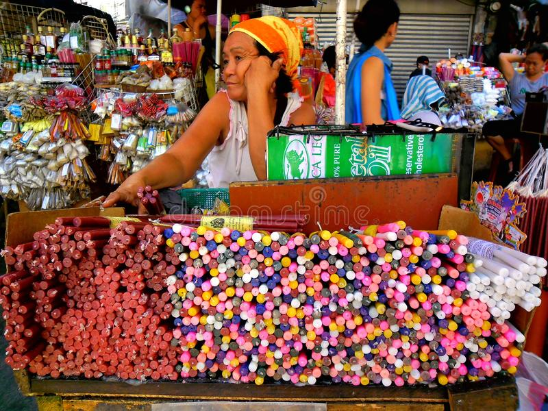 Asian street vendor selling colored candles outside of quiapo church in quiapo, manila, philippines in asia stock photography