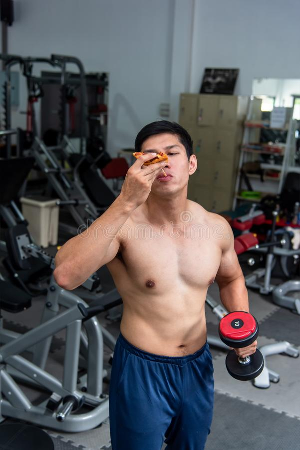 Asian strong man who loves exercising is holding a dumbbell and is eating pizza for getting energy before workout at fitness. Center.Diet and active concept royalty free stock photos