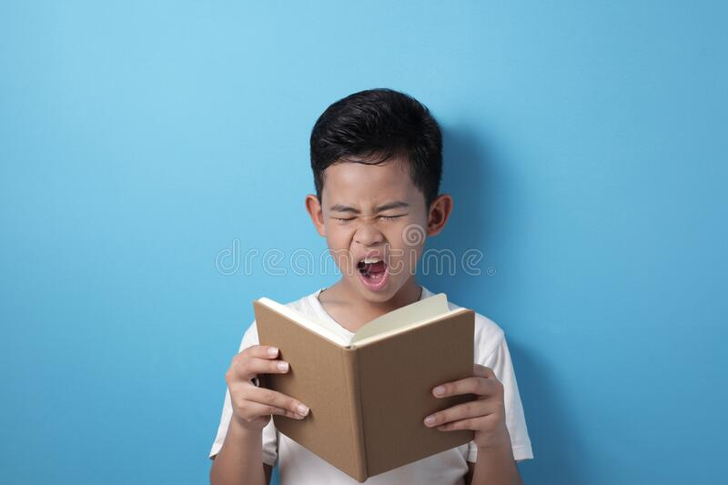 Asian student boy tired sleepy and yawning when reading a book stock image