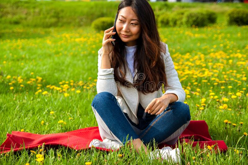 Asian student calling by phone in summer park on green grass. Asian happy woman calling by phone in summer park on green grass royalty free stock images
