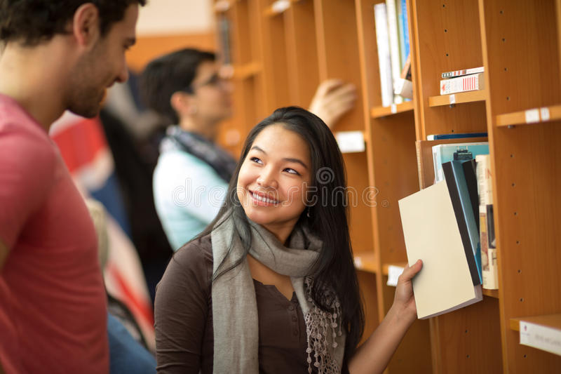 Asian student choosing books in library. Pretty Asian student choosing books with classmate in library stock image