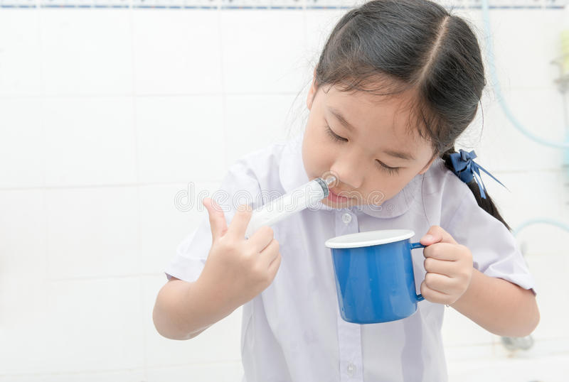 Asian student girl flushing her nose with syringe and saline stock photo