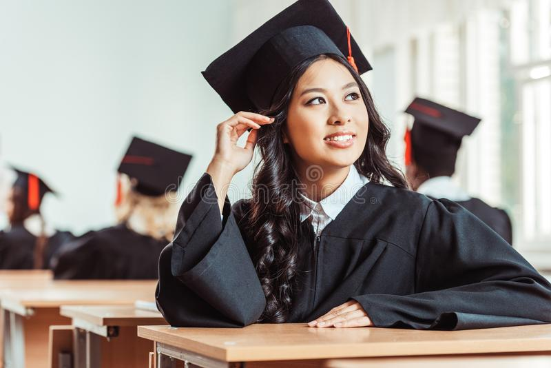 Asian student girl in graduation costume sitting. At classroom stock photos