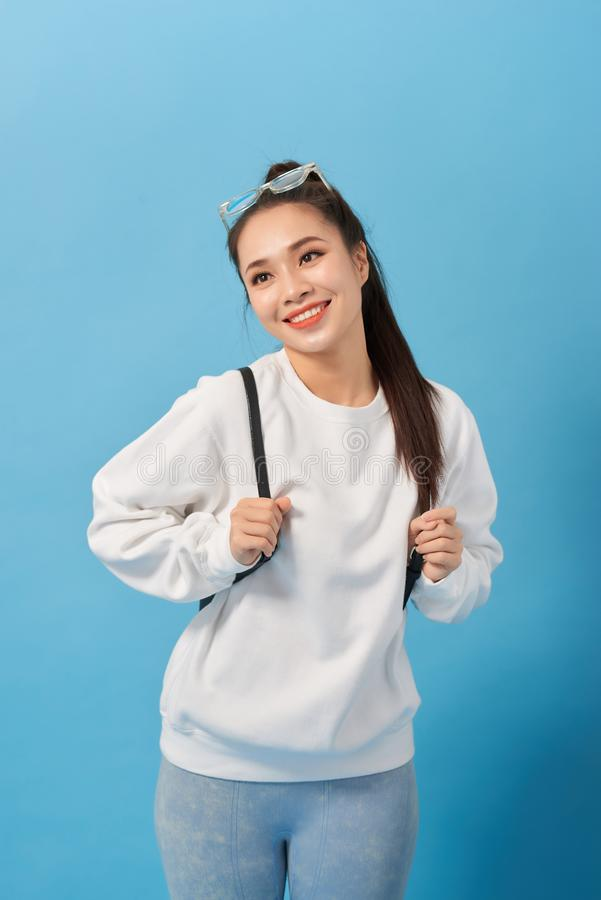 Asian student girl over isolated blue wall happy and smiling stock image