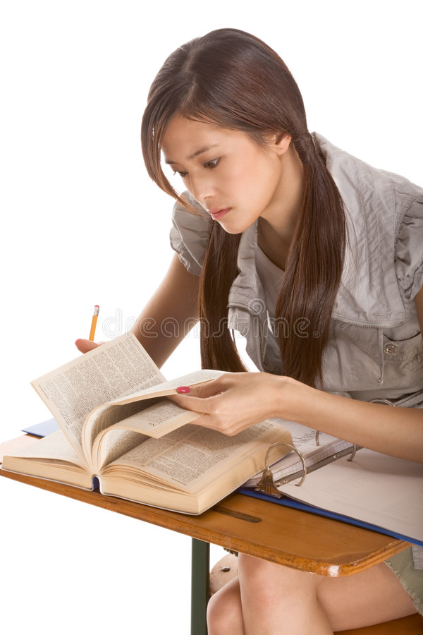 Asian student preparing for spelling-bee contest. Asian student girl sitting by the desk and studying English dictionary in preparation for test, exam or royalty free stock photography