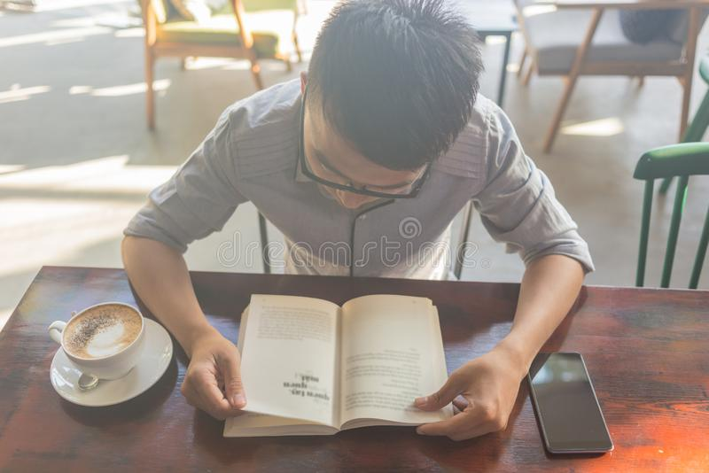 Asian student reading book in the coffee shop stock images