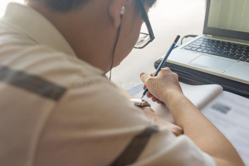 Rear view of student writing on workbook next to laptop royalty free stock photos