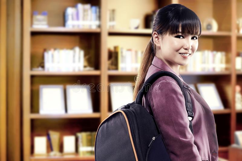 Asian student woman with backpack standing and look back in the university library. Back to School concept stock image