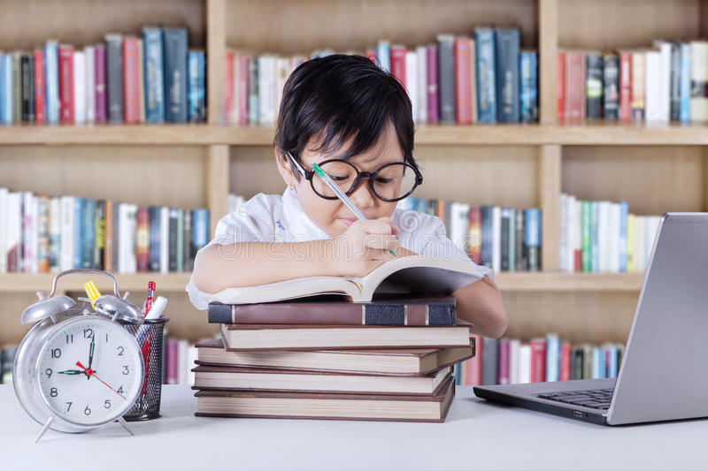 Asian student writes on the book in library royalty free stock photography