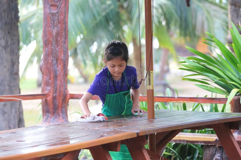Asian Students ,Children working in the restaurant during the summer, Child labor was cleaning in the restaurant. The girl was pulling a large umbrella stock images