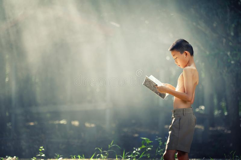 Asian students reading books in Thailand countryside, Rural children are reading a book at the forest.Book knowledge is important royalty free stock images