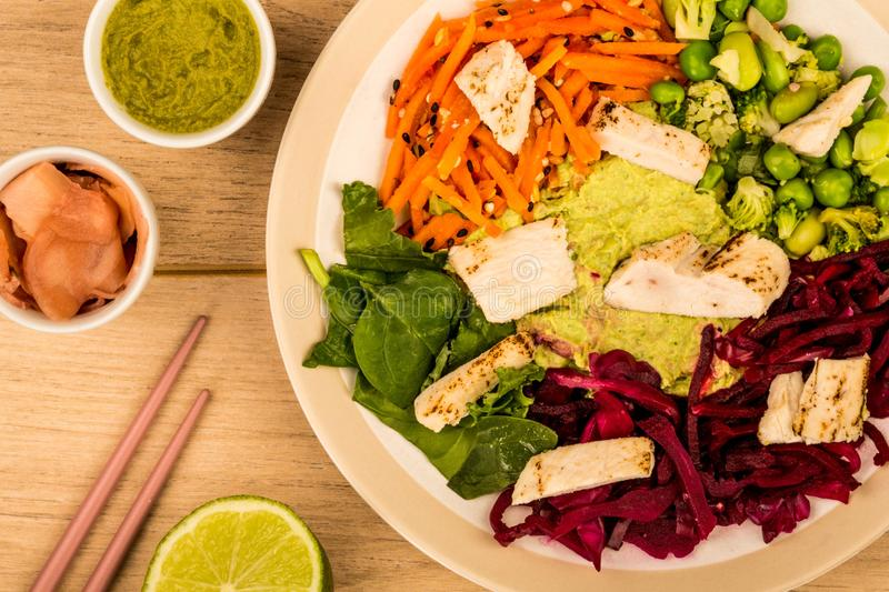 Asian Style Chargrilled Chicken Salad With Red Cabbage Carrots E. Damame Beans and Hummus Against A Light Wooden Background or Tabletop stock photo