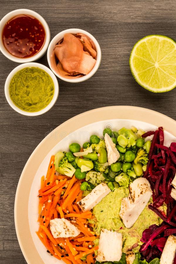 Asian Style Chargrilled Chicken Salad With Red Cabbage Carrots E. Damame Beans and Hummus Against A Dark Wooden Background stock photo
