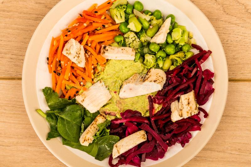 Asian Style Chargrilled Chicken Salad With Red Cabbage Carrots E. Damame Beans and Hummus Against A Light Wooden Background or Tabletop stock images