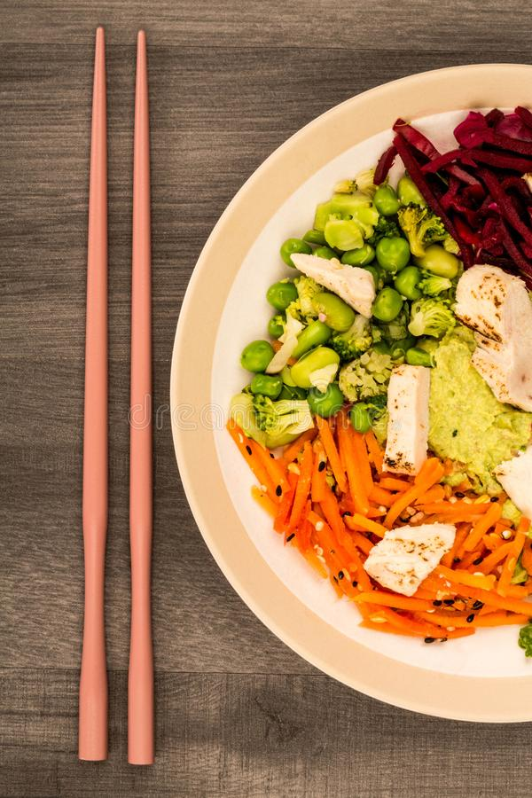 Asian Style Chargrilled Chicken Salad With Red Cabbage Carrots E. Damame Beans and Hummus Against A Dark Wooden Background royalty free stock photos