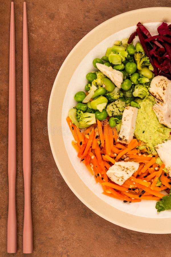 Asian Style Chargrilled Chicken Salad With Red Cabbage Carrots E. Damame Beans and Hummus Against A Red Tiled Background stock photo