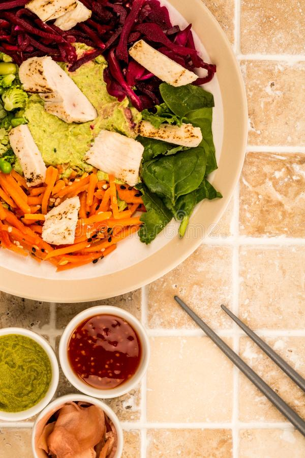Asian Style Chargrilled Chicken Salad With Red Cabbage Carrots E. Damame Beans and Hummus On A Tiled Kitchen Worktop or Counter royalty free stock image