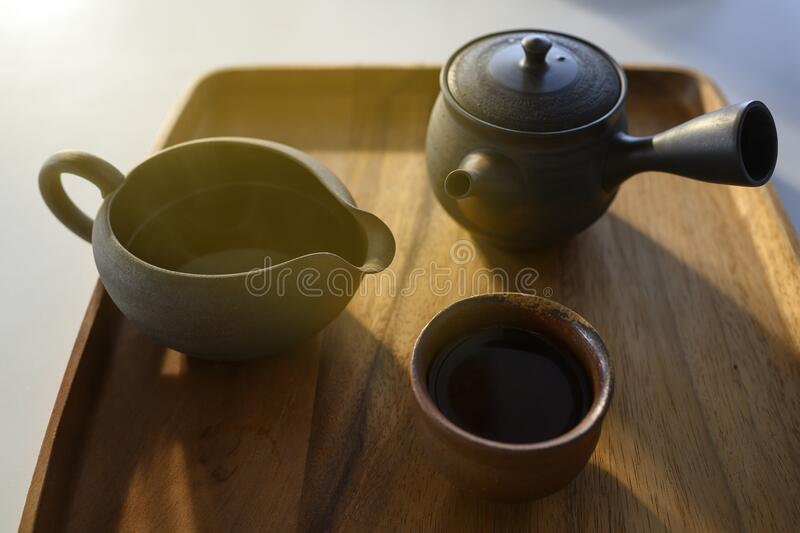 Asian style dark brown clay tea set with wooden tray. Light in the morning from the window stock image