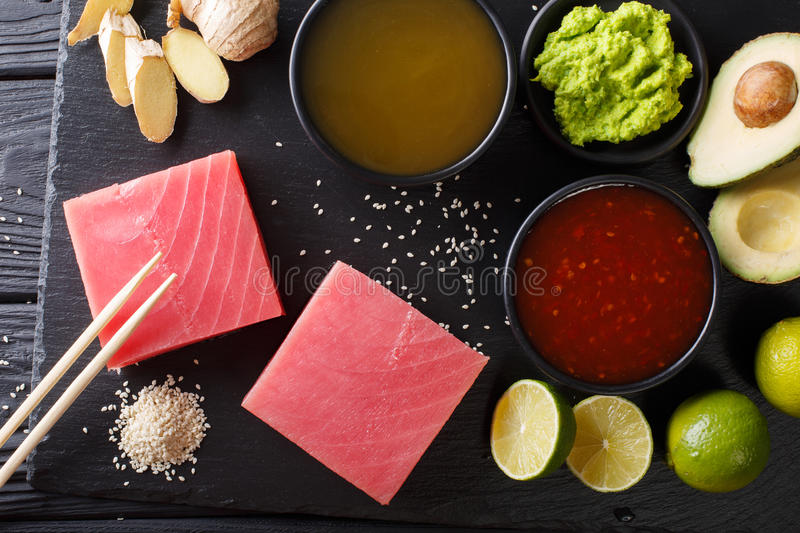 Asian style: Raw fresh tuna with ingredients for cooking close-up. horizontal top view. Asian style: Raw fresh tuna with ingredients for cooking close-up on the stock photos
