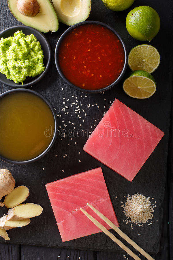 Asian style: Raw fresh tuna with ingredients for cooking close-up. Vertical top view. Asian style: Raw fresh tuna with ingredients for cooking close-up on the stock image
